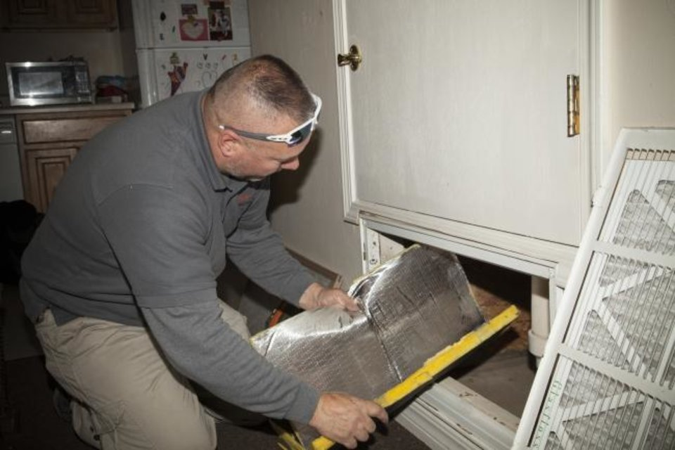 Photo -  A Skyline Energy Solutions employee checks out a central heating and air conditioning unit at Mount Olive Senior Cottages in Oklahoma City on Monday. The company and volunteers from Oklahoma Gas and Electric Co. provided energy-saving upgrades to the cottages Monday and Tuesday as part of an event to honor Martin Luther King Jr. [Provided]