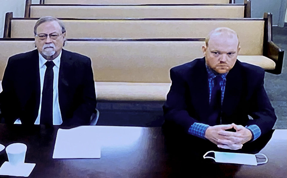 Photo -  In this image made from video, from left, father and son, Gregory and Travis McMichael, accused in the shooting death of Ahmaud Arbery in Georgia in Feb., listen via closed circuit TV Thursday in the Glynn County Detention center in Brunswick, Ga., as lawyers argue for bond to be set at the Glynn County courthouse. The McMichaels chased and fatally shot Ahmaud Arbery, a 25-year-old Black man, after they spotted him running in their neighborhood just outside the port city of Brunswick. [Lewis Levine/The Associated Press]