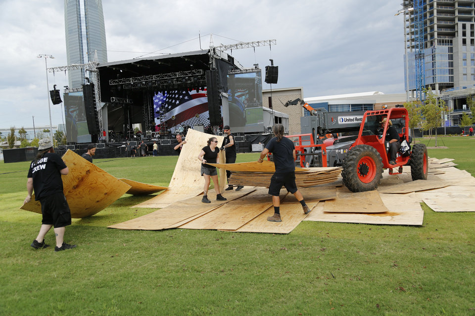 Photo - Workers remove plywood sheets that were set to protect the grass during set up of the sound booth. Preparations are wrapping up for the opening night Kings of Leon concert to kick off the grand opening weekend of Scissortail Park Thursday, September 26, 2019. [Doug Hoke/The Oklahoman]