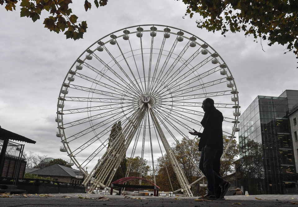 Photo -  A man passes a closed Ferris wheel in the city center of Essen, Germany, Monday, Nov. 2, 2020. A one month long partial lockdown due to the coronavirus pandemic becomes effective in Germany on Monday. (AP Photo/Martin Meissner)