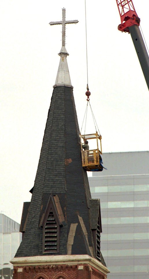 Photo -  A worker puts shingles on the steeple of St. Joseph Old Cathedral in downtown Oklahoma City Tuesday morning. The church is undergoing extensive renovationafter being damaged in the Alfred Murrah Federal Building car bomb explosion on April 19.