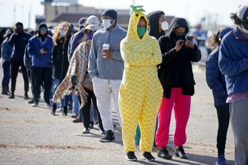 Photo -  Dressed as a pineapple for Halloween, Lawri Sanders, along with her mother Shay Smth, wait in line with other voters outside the Oklahoma County Election Board on the last day of early voting in Oklahoma City, Saturday, Oct. 31, 2020. [Bryan Terry/The Oklahoman]