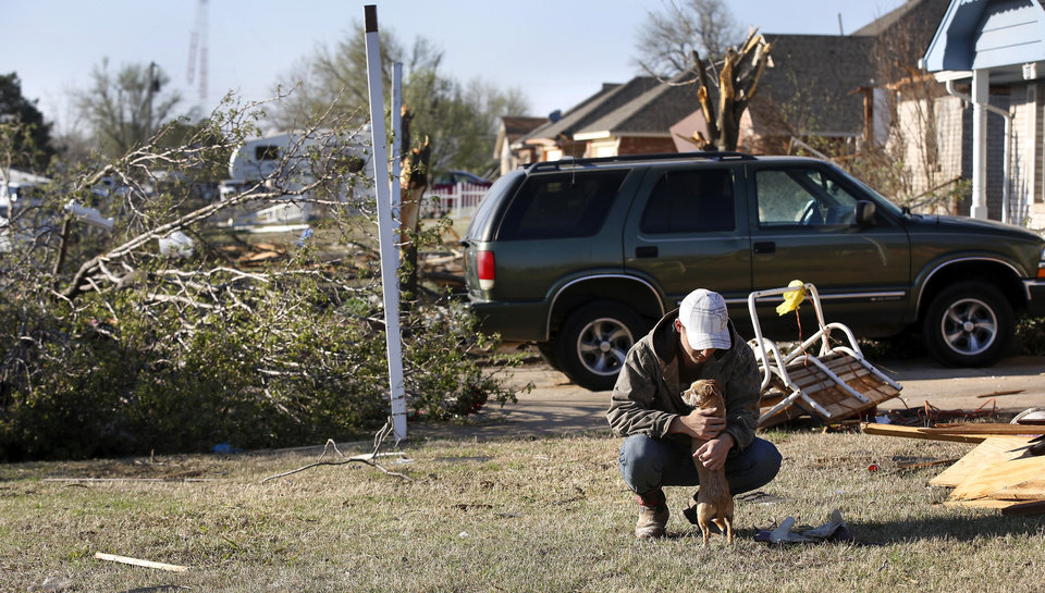 "Photo - Thomas Hutton, 18, spends a moment with his pet chihuahua mix, Scrappy, in front of his home in the 300 block of N. Norman where Hutton, Scrappy and Hutton's dad , Brian, sought shelter in the hallway as the tornado passed through their neighborhood, between NW 5 and Main Street, and between Telephone Rd. and Santa Fe in Moore.  Thomas Hutton said he had very little time to seek shelter. He had just finished taking a shower when he ""opened the bathroom door, and it hit.""  ""I only had seconds,"" Hutton recounted. Thursday morning, March 26, 2015, the day after a tornado damaged homes and a school Wednesday evening. Photo by Jim Beckel, The Oklahoman"