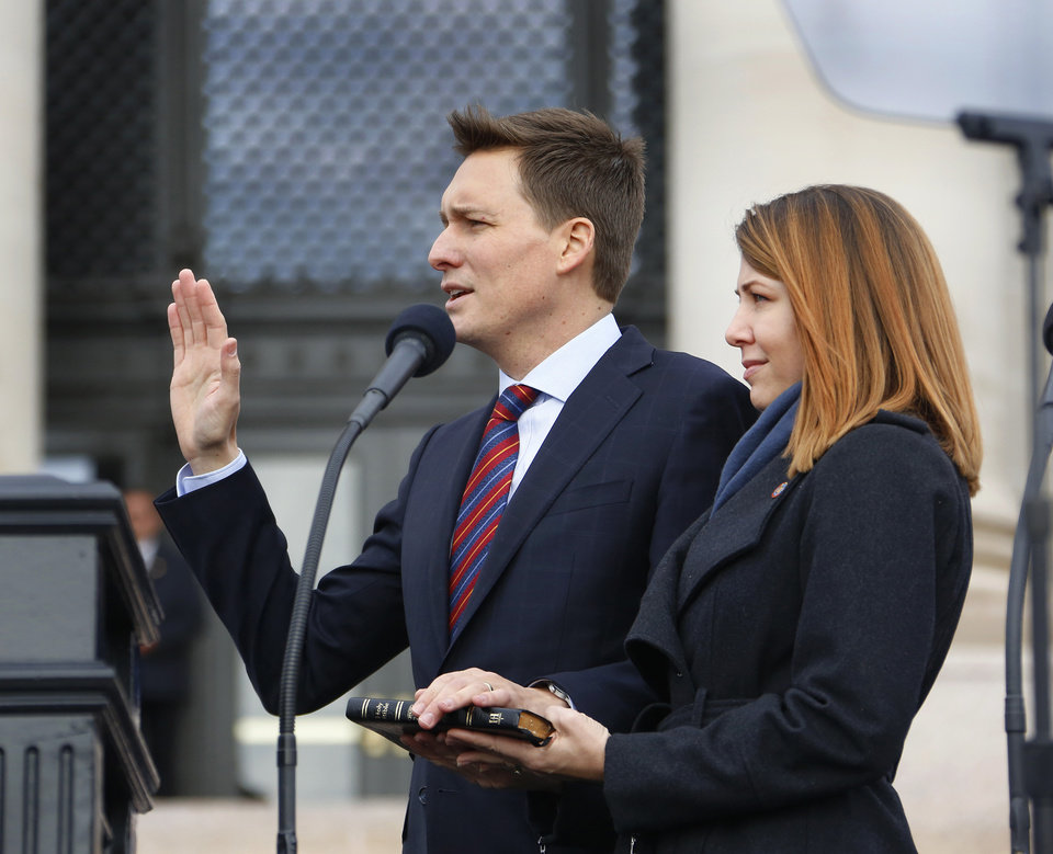 Photo - Lisa Pinnell holds a Bible as her husband, Matt Pinnell is sworn in as Lt. Governor during the inauguration ceremony where Kevin Stitt was sworn in as Oklahoma's 28th governor by Supreme Court Chief Justice Noma Gurich on Monday, Jan. 14, 2019.   Photo by Jim Beckel, The Oklahoman.