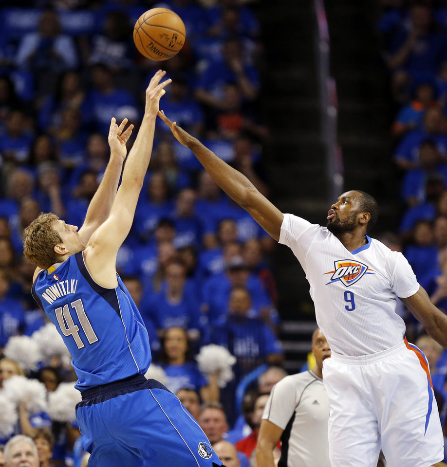 Photo - Oklahoma City's Serge Ibaka, right, defends Dallas' Dirk Nowitzki during Game 5 of the first-round series between the Thunder and Dallas Mavericks in the NBA playoffs at Chesapeake Energy Arena. Ibaka traditionally terrorizes the San Antonio Spurs, the Thunder's opponent in the next series. (By Nate Billings, The Oklahoman)
