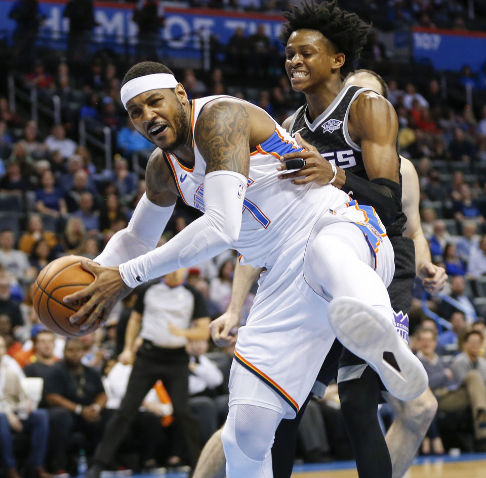 Photo - Oklahoma City's Carmelo Anthony (7) grabs a rebound in front of Sacramento's De'Aaron Fox (5) during an NBA basketball game between the Oklahoma City Thunder and the Sacramento Kings at Chesapeake Energy Arena in Oklahoma City, Monday, March 12, 2018. Oklahoma City won 106-101. Photo by Nate Billings, The Oklahoman