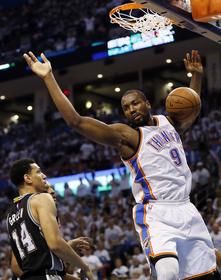 Photo - Oklahoma City's Serge Ibaka (9) comes down after dunking the ball in front of San Antonio's Danny Green (14) during Game 4 of the Western Conference semifinals between the Oklahoma City Thunder and the San Antonio Spurs in the NBA playoffs at Chesapeake Energy Arena in Oklahoma City, Sunday, May 8, 2016. Photo by Nate Billings, The Oklahoman