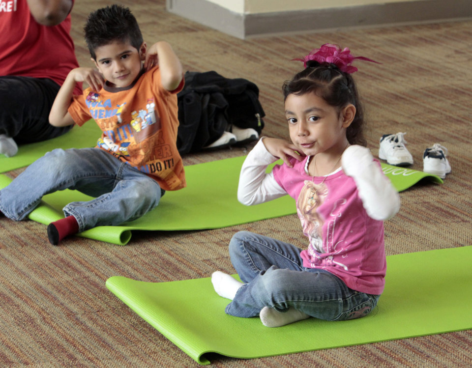 Photo - Aaron Secondino and Melissa Valdez listen and pose as Angela Moorad teaches yoga to three and four-year-olds on Wednesday, March 7, 2012, in Oklahoma City, Okla.  Photo by Steve Sisney, The Oklahoman