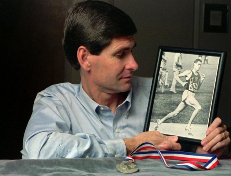 Photo -  Former Olympian Jim Ryun looks at a photograph taken of him in 1968 Olympics in Mexico City where he won a silver medal, foreground, in the 1,500-meter run, at his home in Lawrence, Kansas in 1991. [AP file Photo/Jeff Carney]