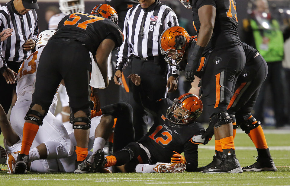 Photo - Oklahoma State's Daxx Garman (12) is helped up by teammates after a sack during the college football game between the Oklahoma State University Cowboys (OSU) the University of Texas Longhorns (UT) at Boone Pickens Staduim in Stillwater, Okla. on Saturday, Nov. 15, 2014.  Photo by Chris Landsberger, The Oklahoman