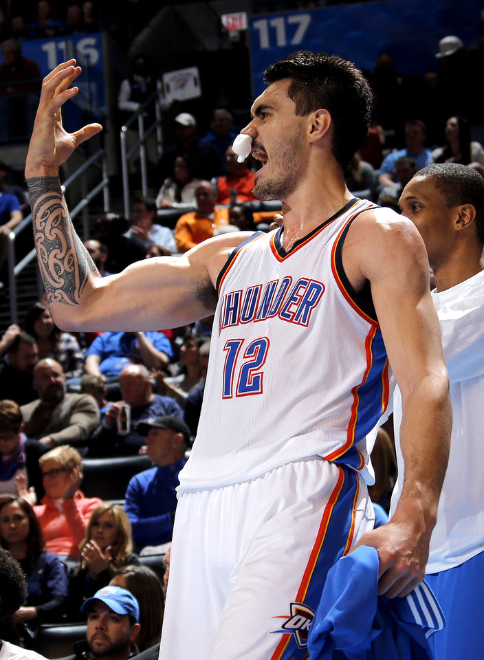Photo - Oklahoma City's Steven Adams (12) celebrates from the bench during the NBA basketball game between the Oklahoma City Thunder and the Charlotte Hornets at the Chesapeake Energy Arena in Oklahoma City, Friday, Dec. 26, 2014. Photo by Sarah Phipps, The Oklahoman
