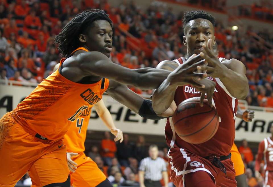 Photo - Oklahoma's Kristian Doolittle (21) goes for the ball beside Oklahoma State's Isaac Likekele (13) during a Bedlam basketball game between the Oklahoma State Cowboys (OSU) and the University of Oklahoma Sooners (OU) at Gallagher-Iba Arena in Stillwater, Okla., Wednesday, Jan. 23, 2019. Oklahoma won70-61. Photo by Bryan Terry, The Oklahoman