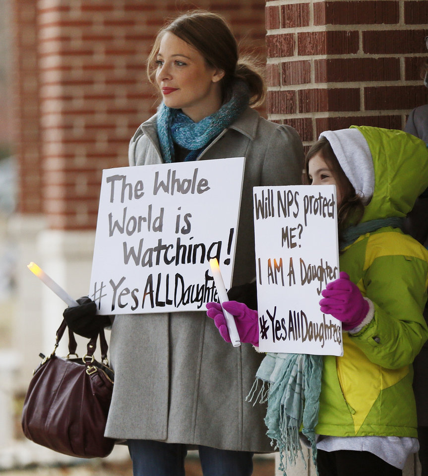 Photo - Jenny Ellis, left, of Norman, and her daughter Emily Ellis-Collett, 8, hold signs during a candlelight vigil outside the Board of Education meeting for Norman Public Schools at 131 S. Flood in Norman, Okla., Monday, Dec. 1, 2014. The vigil was in response to sexual assaults and bullying at Norman High School. Photo by Nate Billings, The Oklahoman