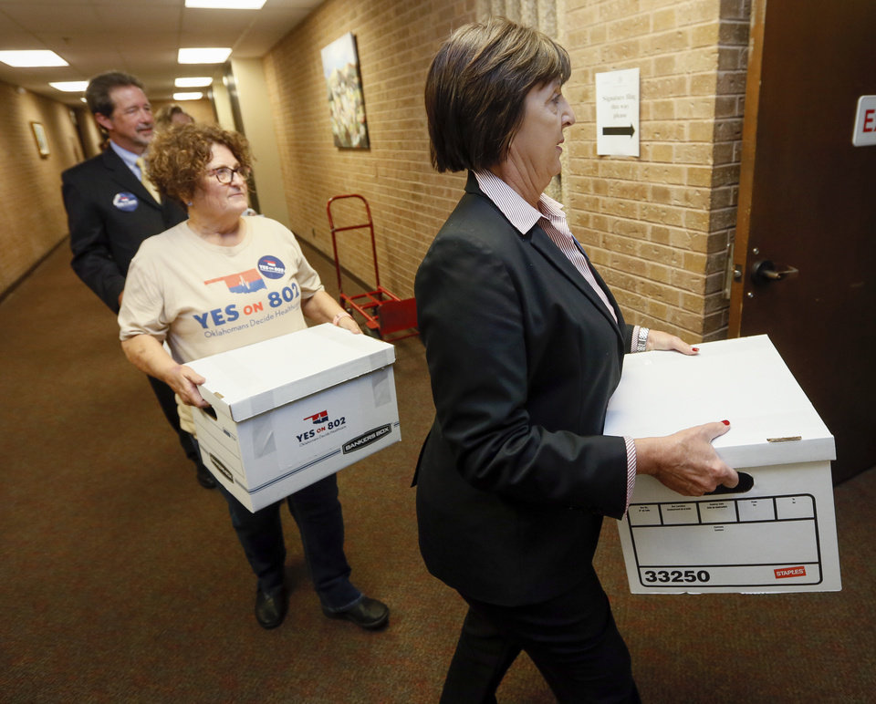 Photo - Patti Davis, president of the Oklahoma Hospital Association, leads supporters of Yes on 802, the campaign to put a Medicaid expansion state question on the ballot, as they deliver petitions to the Oklahoma Secretary of State's office in Oklahoma City, Thursday, Oct. 24, 2019. [Nate Billings/The Oklahoman]
