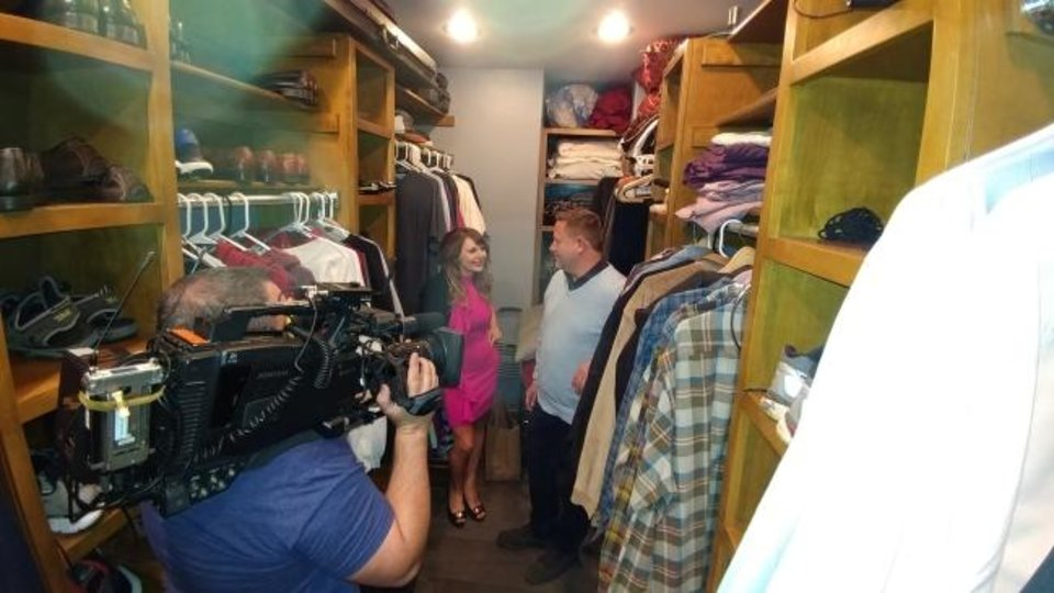 Photo -  Denise and Troy Schroder, in back, are recorded inside a master closet by camera operator Chris McCaffrey for an episode of