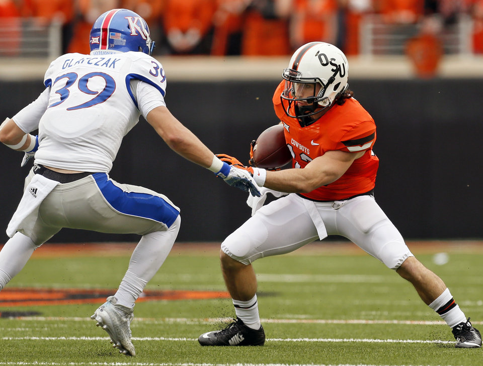 Photo - Oklahoma State's David Glidden (13) rains after a catch against Kansas' Michael Glatczak (39) during a college football game between the Oklahoma State University Cowboys (OSU) and the Kansas Jayhawks (KU) in Stillwater, Okla., Saturday, Oct. 24, 2015. Photo by Nate Billings, The Oklahoman