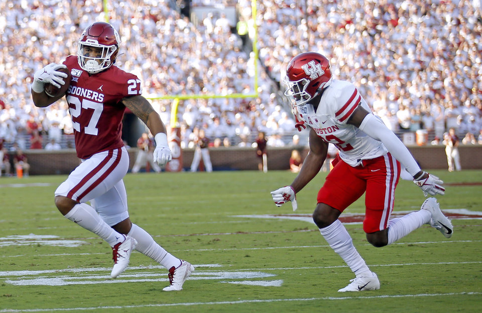 Photo - Oklahoma's Jeremiah Hall runs toward a touchdown as Houston's Gervarrius Owens (32) chases him during a college football game between the University of Oklahoma Sooners (OU) and the Houston Cougars at Gaylord Family-Oklahoma Memorial Stadium in Norman, Okla., Sunday, Sept. 1, 2019. [Sarah Phipps/The Oklahoman]