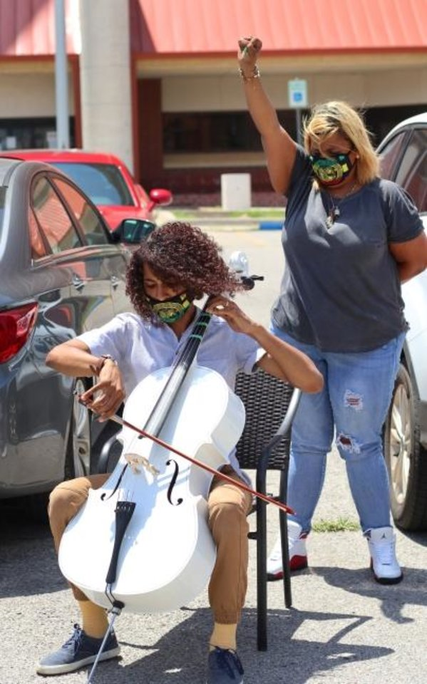 Photo -  Tyreke Baker, plays his cello, with his mother Teresa Baker behind him, before turning himself in to face a charge of incitement to riot at the Oklahoma County Jail on Wednesday. [Doug Hoke/The Oklahoman]
