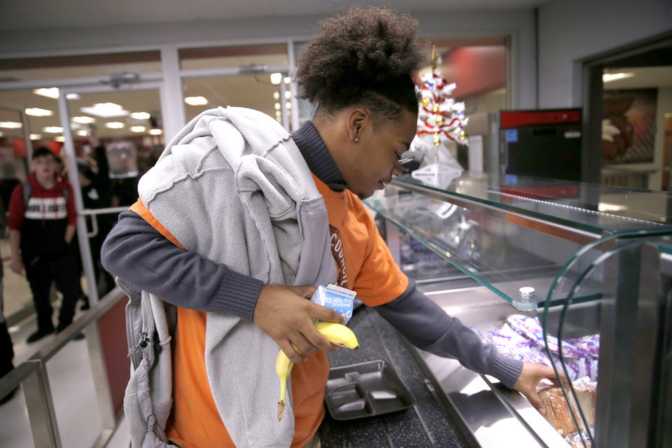 Photo -  Student Kevin Quillen gets a late-afternoon meal at Capitol Hill High School on Thursday. [Photo by Sarah Phipps, The Oklahoman]