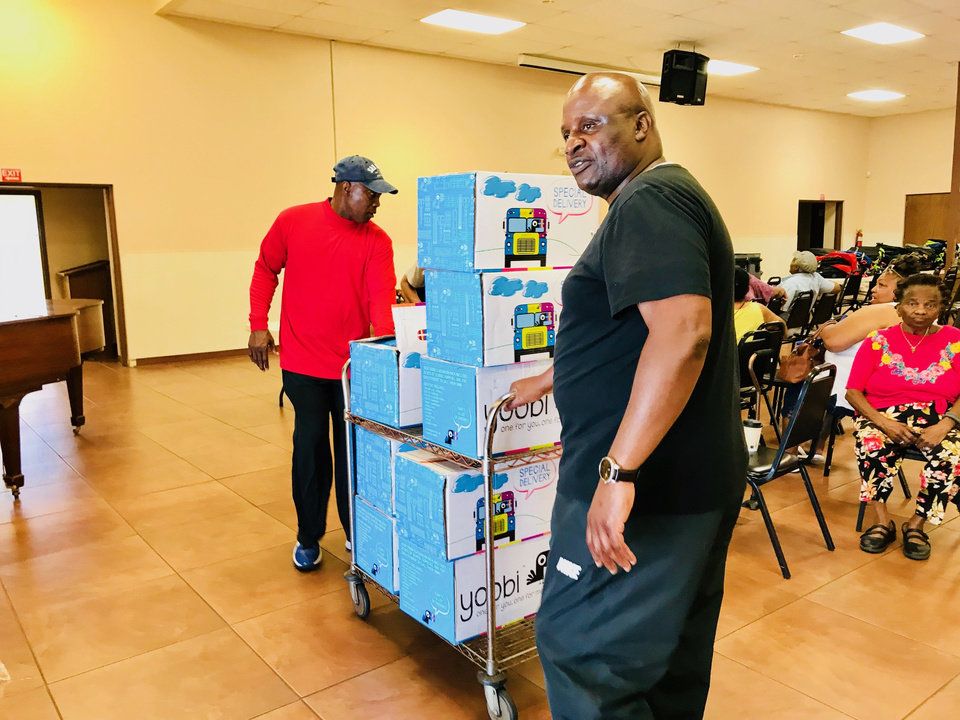 Photo -  The Rev. Calvin Cage of Washington, D.C., and the Rev. John Johnson of Greenville, Miss., bring items for a food distribution and supply giveaway into the Fairview Baptist Church fellowship hall on Friday at 1700 NE 7. [Photo by Carla Hinton, The Oklahoman]