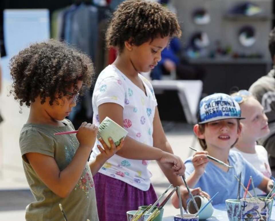 Photo -  From left, Phoebe Dyer, 5, Ainsley Dyer, 8, Bentley Mendoza, 7, and Scout Howell-Dowd, 8, decorate pottery at Pottery Place during the 2018 Festival of the Arts in downtown Oklahoma City. [Nate Billings/The Oklahoman]