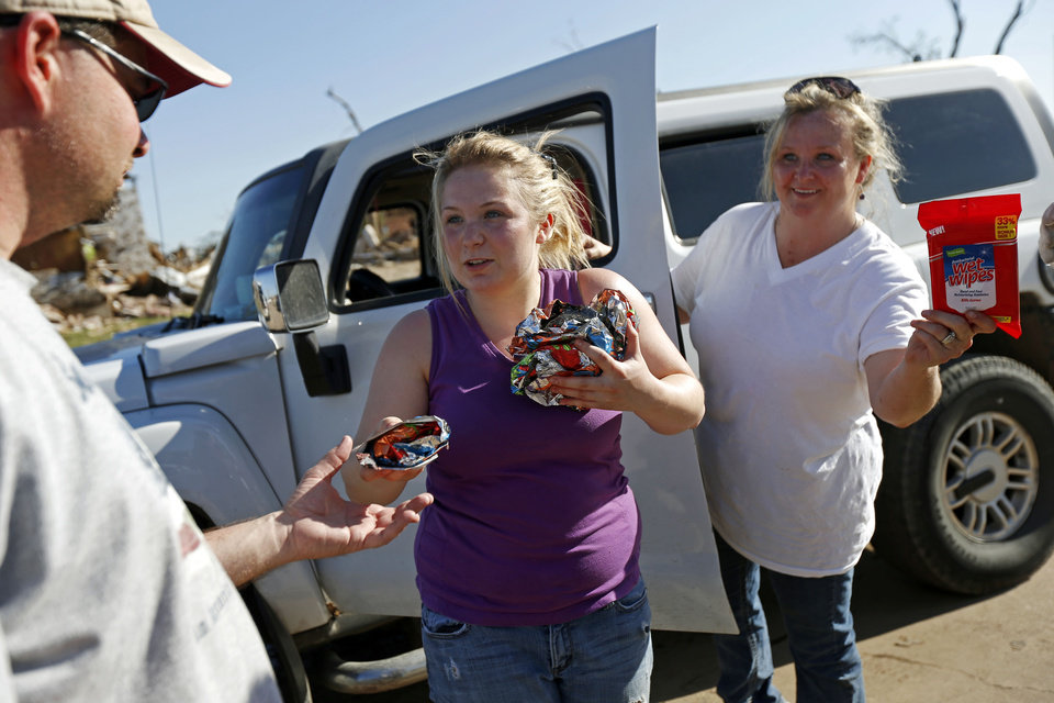Photo - Brooklyn Shoop, left, and her mother Christina Silvers of Kansas City, Mo., pass out food, water, and supplies to tornado victims in the Plaza Towers neighborhood in Moore, Okla., on Wednesday, May 22, 2013. The two also passed out items after the Joplin tornado. The area was heavily damaged by a  tornado that struck on Monday, May 20, 2013. Photo by Bryan Terry, The Oklahoman