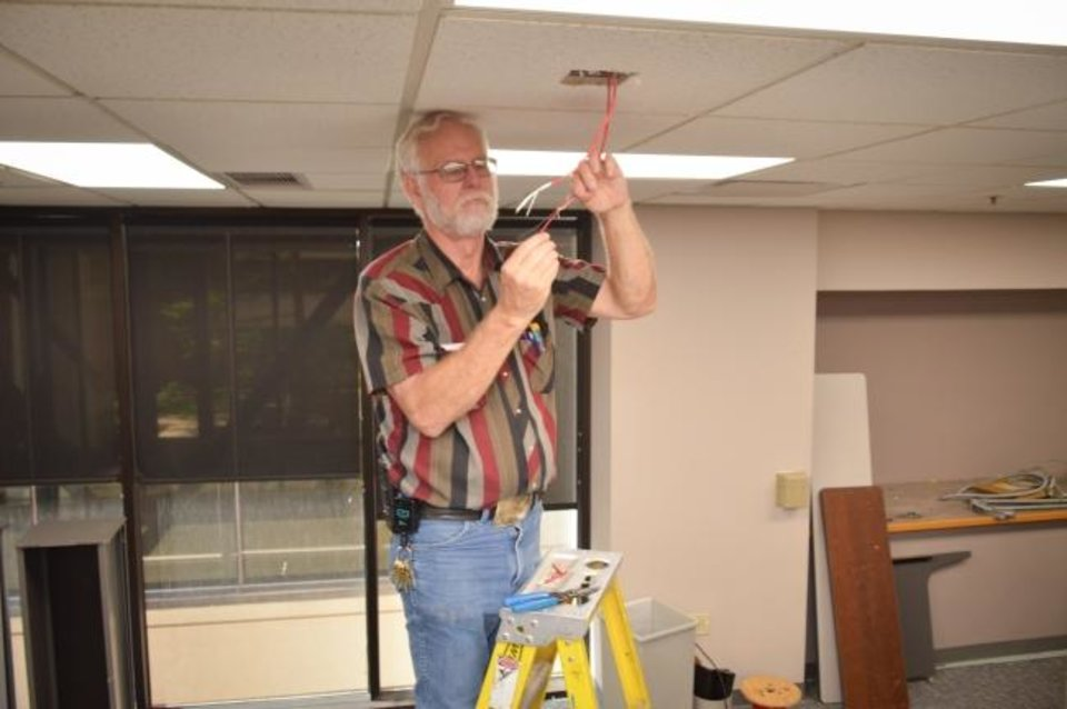Photo -  Oklahoma Medical Research Foundation electrician Bruce Clark at work prior to the Covid-19 pandemic. [Photo Provided]