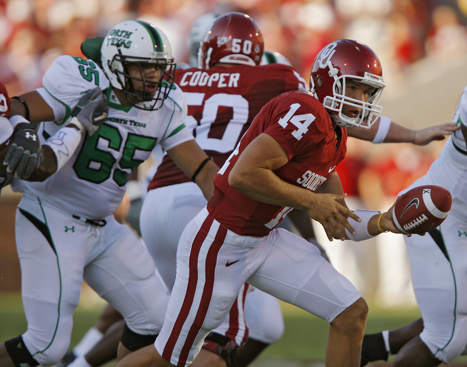 Photo - Oklahoma quarterback Sam Bradford (14) looks to hand off the ball in the first half during the University of Oklahoma Sooners (OU) college football game against the University of North Texas Mean Green (UNT) at the Gaylord Family - Oklahoma Memorial Stadium, on Saturday, Sept. 1, 2007, in Norman, Okla.