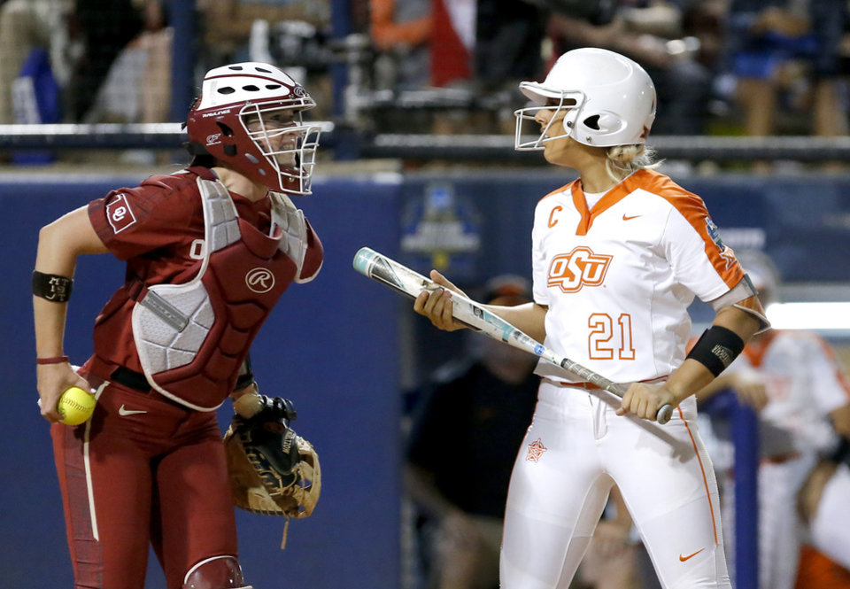 Photo - Oklahoma's Lynnsie Elam, left, celebrates after Oklahoma State's Sydney Pennington (21) struck out during the fifth inning of an NCAA softball Women's College World Series game in Oklahoma City, Friday, May 31, 2019. (Sarah Phipps/The Oklahoman via AP)