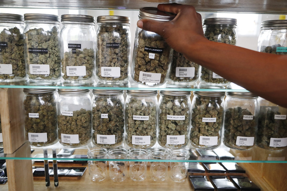 Photo - In this Tuesday, Oct. 2, 2018, photo, a clerk reaches for a container of marijuana buds for a customer at a medical marijuana dispensary in Detroit, Michigan. (AP Photo/Carlos Osorio)
