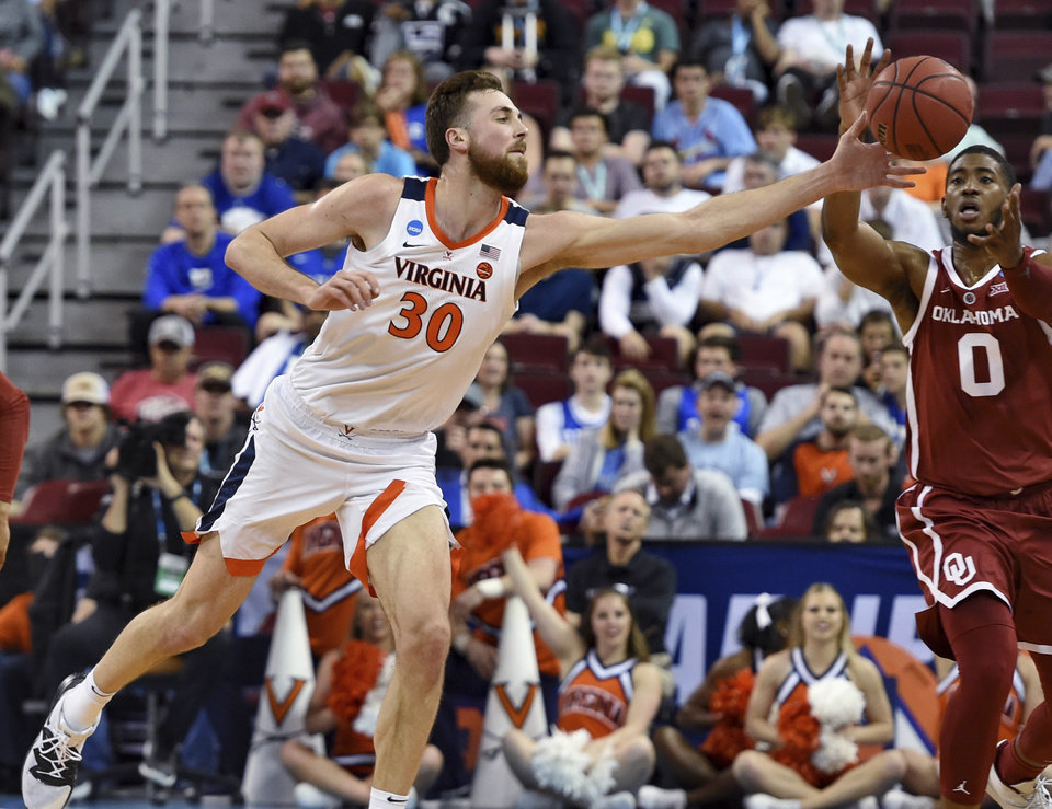 Photo - Virginia's Jay Huff stretches out for a loose ball against Oklahoma's Christian James (0) during the second half of a second-round men's college basketball game in the NCAA Tournament in Columbia, S.C., Sunday, March 24, 2019. (AP Photo/Richard Shiro)