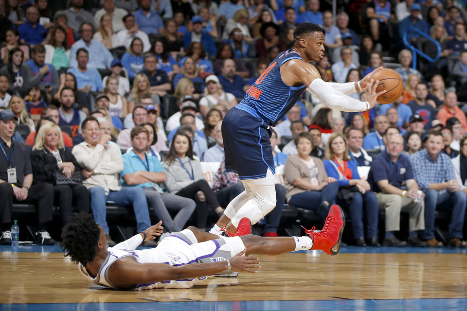 Photo - Oklahoma City's Russell Westbrook (0) passes the ball as Sacramento's De'Aaron Fox (5) falls down during an NBA basketball game between the Oklahoma City Thunder and the Sacramento Kings at Chesapeake Energy Arena in Oklahoma City, Sunday, Oct. 21, 2018. Photo by Bryan Terry, The Oklahoman