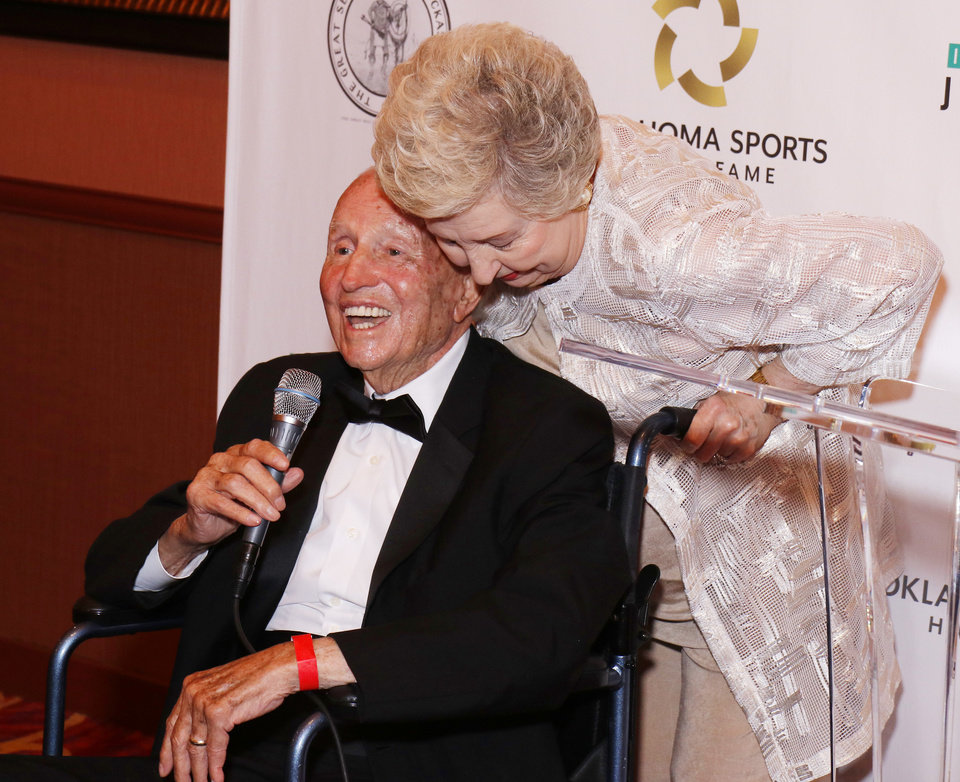 Photo - Mary Henson leaves over her husband Lou Henson during a media conference before the Oklahoma Sports Hall of Fame ceremony at Riverwind Casino in Norman Monday, August 12, 2019. [Doug Hoke/The Oklahoman]