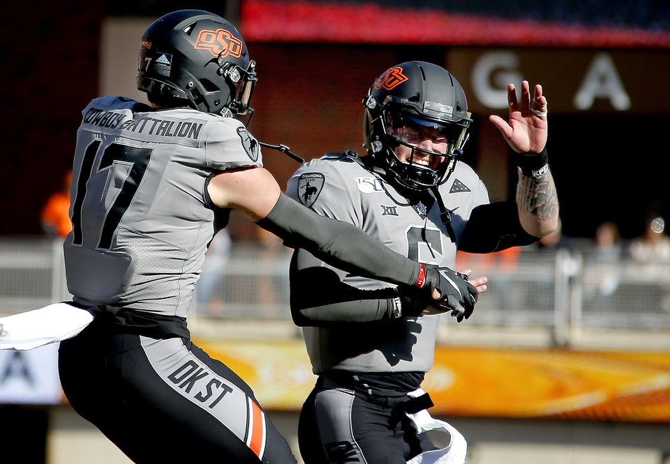 Photo - Oklahoma State's Dillon Stoner (17) celebrates his touchdown pass with Oklahoma State's Dru Brown (6) in the fourth quarter during the college football game between the Oklahoma State University Cowboys and the Kansas Jayhawks at Boone Pickens Stadium in Stillwater, Okla., Saturday, Nov. 16, 2019. OSU won 31-13. [Sarah Phipps/The Oklahoman]
