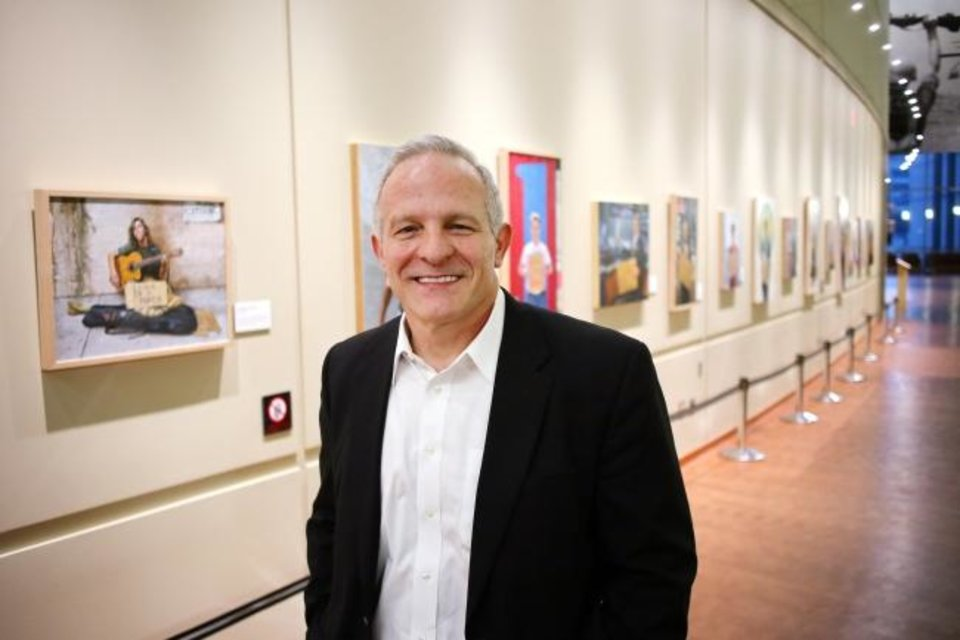Photo -  Georgia-based Oklahoma native Mike Wimmer stands in front of an exhibit of his paintings at the Oklahoma History Center on March 21. [Doug Hoke/The Oklahoman]