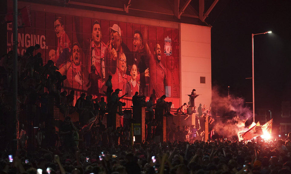 Photo -  Liverpool supporters celebrate as they gather outside of Anfield Stadium in Liverpool, England, Friday, June 26, 2020 after Liverpool clinched the English Premier League title. Liverpool took the title after Manchester City failed to beat Chelsea on Wednesday evening. (AP photo/Jon Super)