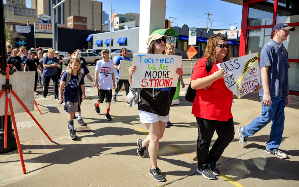 Photo - Moore Public School teachers, students and supporters walk through downtown Oklahoma City, Okla. on Thursday, April 12, 2018, as they make their way to the Capitol to take part in the ongoing teacher walkout. A group of Moore teachers chose to continue their walkout after administrators told teachers to return to class on Thursday.    Photo by Chris Landsberger, The Oklahoman