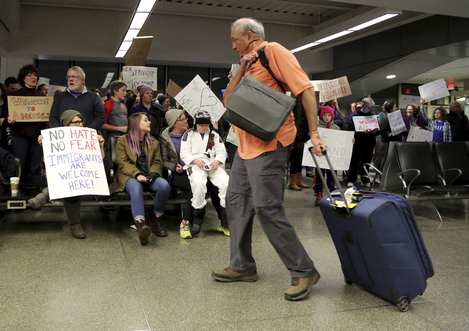 Photo - Travelers arriving to at the international gate of the Minneapolis-St. Paul International Airport are greeted by protesters demonstrating against an executive order signed by President Donald Trump, restricting immigration from several Muslim nations Saturday, Jan. 28, 2017, in Minneapolis. (David Joles/Star Tribune via AP)