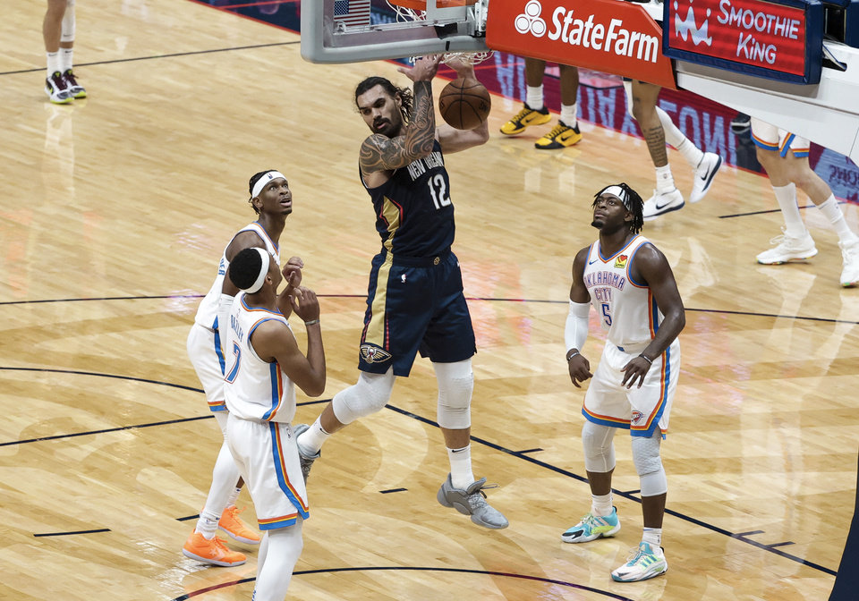 Photo - New Orleans Pelicans center Steven Adams (12) dunks past Oklahoma City Thunder forward Darius Bazley (7) and guard Shai Gilgeous-Alexander (2) and guard Luguentz Dort (5) in the third quarter of an NBA basketball game in New Orleans, Wednesday, Jan. 6, 2021. (AP Photo/Derick Hingle)