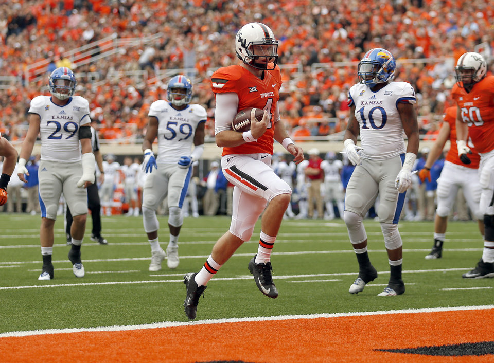 Photo - Oklahoma State's J.W. Walsh (4) scores a touchdown in the first quarter during a college football game between the Oklahoma State University Cowboys (OSU) and the Kansas Jayhawks (KU) at Boone Pickens Stadium in Stillwater, Okla., Saturday, Oct. 24, 2015. Photo by Sarah Phipps, The Oklahoman