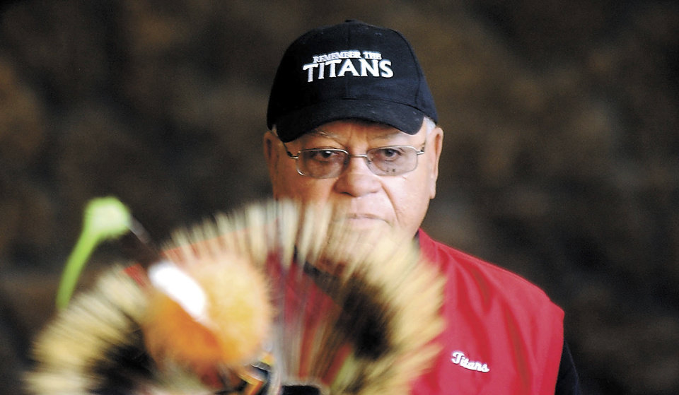 "Photo - File-This Feb. 22, 2005, file photo shows Herman Boone, the coach featured in the movie ""Remember the Titans,"" peering over the headdress of a Shoshone-Bannock dancer to speak to a large crowd in Pocatello, Idaho. Boone, the Virginia high school football coach who inspired the movie ""Remember the Titans,"" has died. He was 84.  Boone guided T.C. Williams High School to a state championship while navigating the early days of desegregation.  Aly Khan Johnson, an assistant coach for Boone beginning in 1972, said the coach died Wednesday, Dec. 18, 2019, at his home In Alexandria, Virginia. Johnson said a funeral home operated by his wife is handling the arrangements, which are not complete.(Joshua Duplechian/The Idaho State Journal via AP, File)"