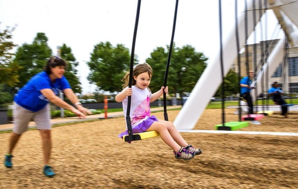 Photo - Stephanie gives her granddaughter, Charleigh, 4,  a push as she takes a ride on The Musical Swings set up at Bicentennial Park in Oklahoma City, Okla. on Monday, Sept. 23, 2019. The swings are set up in part of the Oklahoma City Community Foundation's 50th anniversary.  [Chris Landsberger/The Oklahoman]
