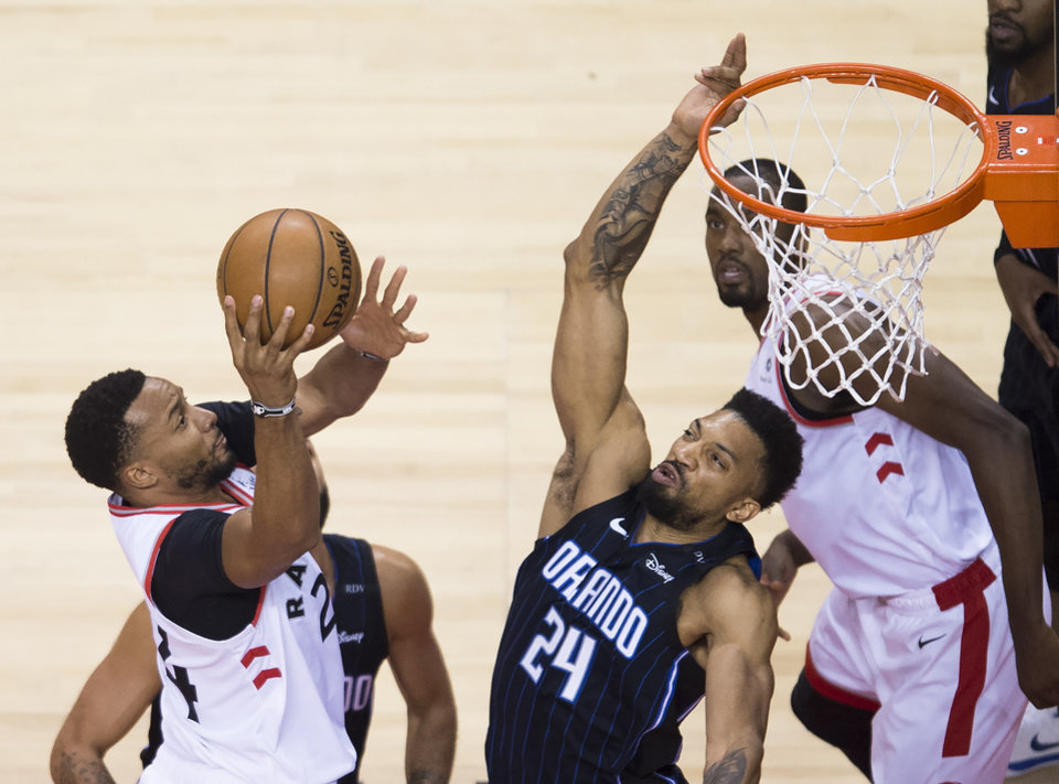 Photo -  Toronto Raptors forward Norman Powell, left, drives to the net against Orlando Magic center Khem Birch (24) during the second half in Game 5 of a first-round playoff series, Tuesday in Toronto. [Nathan Denette/Canadian Press via AP]