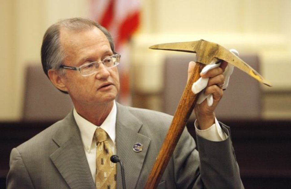 Photo -  Oklahoma Historical Society executive director Bob Blackburn holds the pick ax that was used to break ground for the state Capitol building on July 20, 1914, during a news conference where Blackburn and other state officials previewed a $120 million renovation project they said will prepare the building for its next 100 years of service, in Oklahoma City. [Oklahoman Archive Photo]