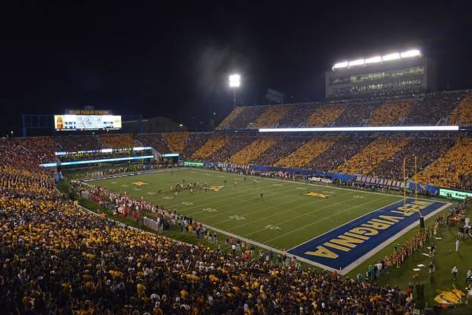 Photo -  The West Virginia fans striped Milan Puskar Stadium with alternate blue and gold Saturday night during the OU-WVU game. (AP Photo)