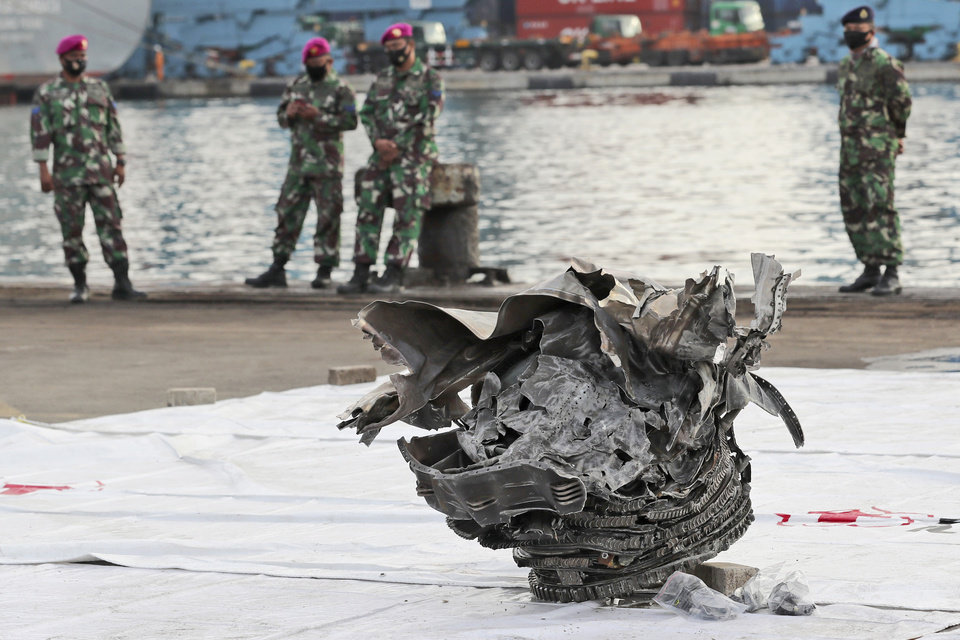 Photo -  Indonesian marines look at a large part of a plane recovered from the waters off Java Island where Sriwijaya Air flight SJ-182 crashed on Saturday, at Tanjung Priok Port in Jakarta, Indonesia, Monday, Jan. 11, 2021. The search for the black boxes of the crashed Sriwijaya Air jet intensified Monday to boost the investigation into what caused the plane carrying 62 people to nosedive at high velocity into the Java Sea. (AP Photo/Tatan Syuflana)