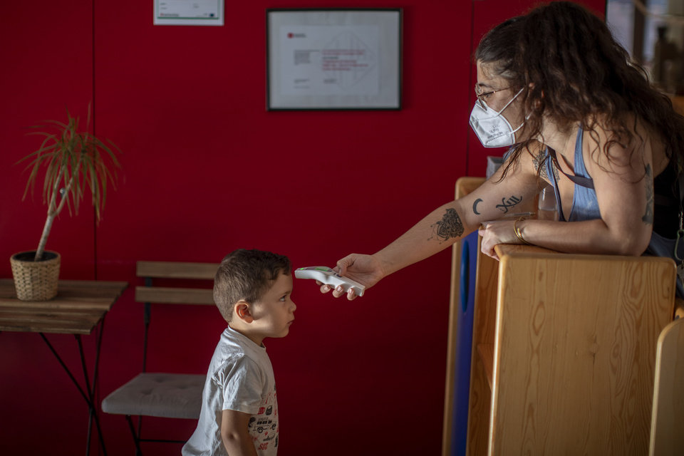 Photo -  Hugo, 3, has his temperature taken by a teacher, Friday, as he arrives at Cobi kindergarten in Barcelona, Spain. [Emilio Morenatti/The Associated PRess]
