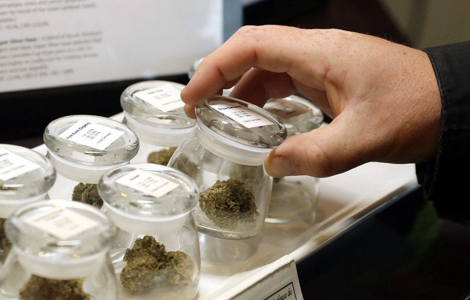Photo - In this Sept. 24, 2018 photo, different strains of marijuana are displayed for sale at a medical marijuana dispensary in Canada. With cannabis still illegal at the federal level in the U.S., Oklahoma banks are hesitant to work with the industry. (AP Photo/Ted S. Warren)
