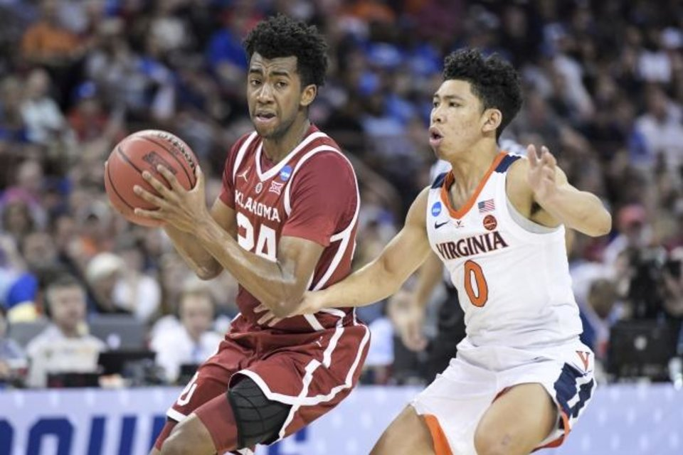 Photo -  OU guard Jamal Bieniemy, left, tries to get past Virginia guard Kihei Clark during a second-round game at the NCAA Tournament on Sunday in Columbia, S.C. [AP Photo/Sean Rayford]