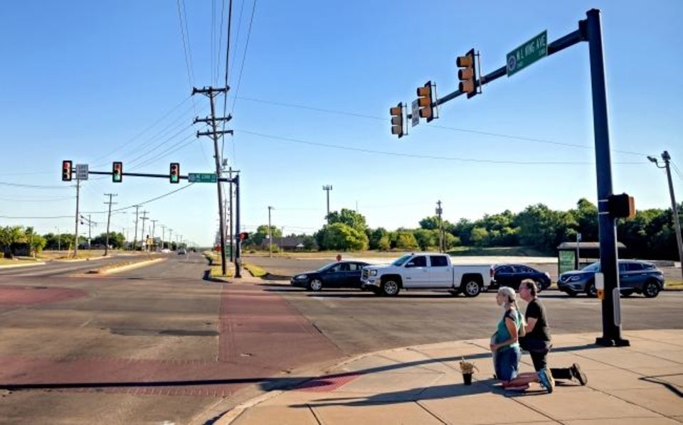 Photo -  Terry Fife and her husband, Ben Hardcastle, kneel on the corner of NE 23 and Martin Luther King Avenue as morning traffic passes through the intersection. [Chris Landsberger/The Oklahoman]